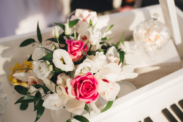 Wedding flower arrangement of white eustoma, orchid and pink roses Premium Photo