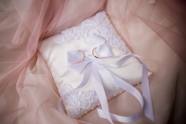 小さな枕の上の結婚式の金の指輪 Premium写真