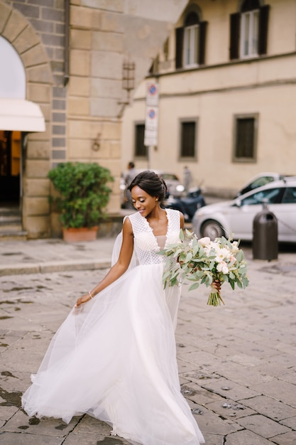 イタリア、フィレンツェでの結婚式。彼女のウェディングドレスと一緒に歩いているアフリカ系アメリカ人の女性 Premium写真