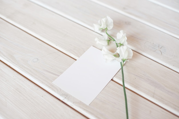 Wedding invitation birthday gift certificate for a spa or care decorated letter card on a white wooden table with a branch of white flowers. Premium Photo
