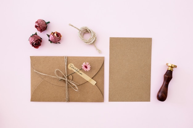 Wedding invitation of kraft paper on pink color background Free Photo