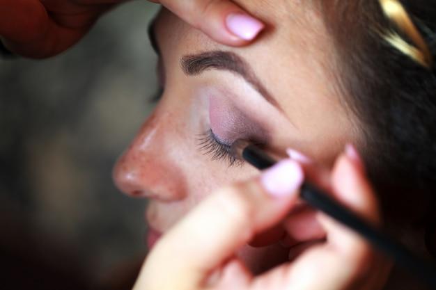 Wedding makeup artist making a make up for bride Premium Photo