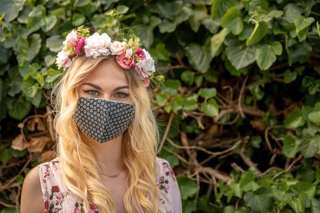 彼女の頭に花の花輪と彼女の口にマスクを持つドレスを着た女性の結婚式の肖像画。コロナウイルス流行時の対策 Premium写真