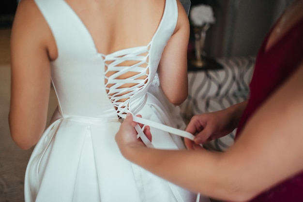 Wedding preparations. helping the bride to put her wedding dress on. Free Photo