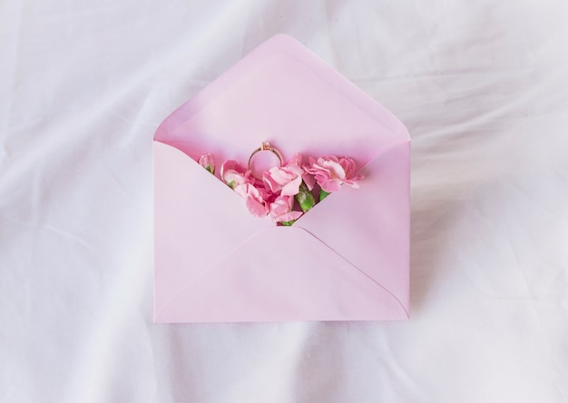 Wedding ring in envelope with flowers Free Photo