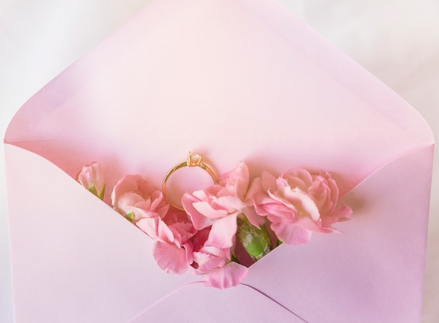 Wedding ring in envelope with pink flowers Free Photo