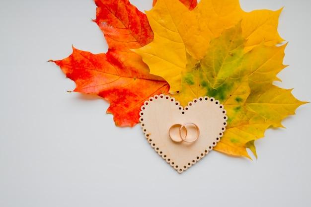 Обручальное кольцо на деревянном сердце на предпосылке листьев осени. золотые обручальные кольца Premium Фотографии