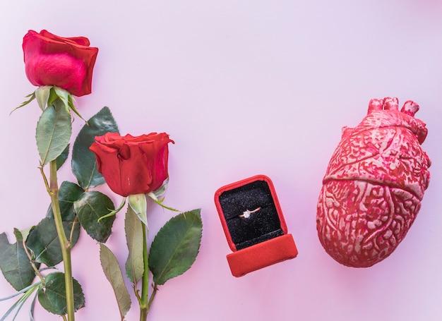 Fede nuziale con cuore umano in ceramica sul tavolo Foto Gratuite