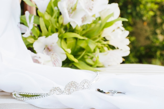 Wedding rings; crown; scarf near the flower bouquet on table Free Photo