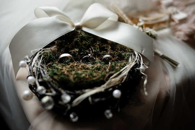 Wedding rings on the decorated nest with greenery and white ribbon Free Photo
