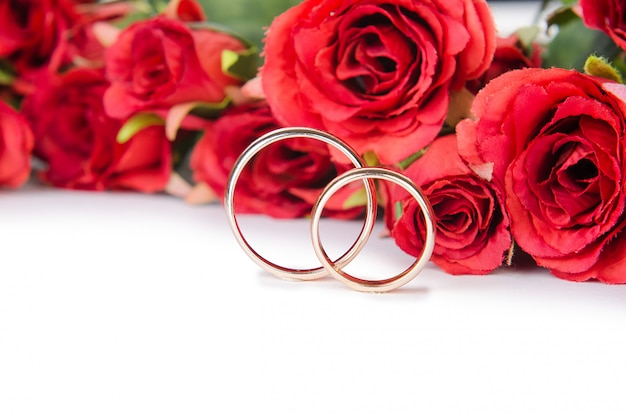 Wedding rings and flowers isolated on white background Premium Photo