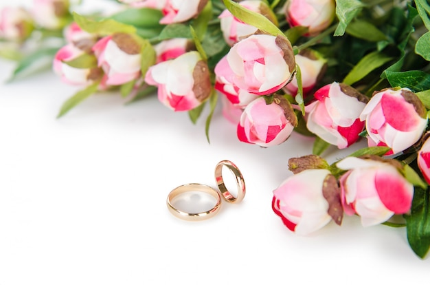 Wedding rings and flowers isolated on white Premium Photo