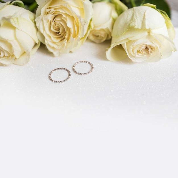 Wedding rings and fresh roses on white background Free Photo