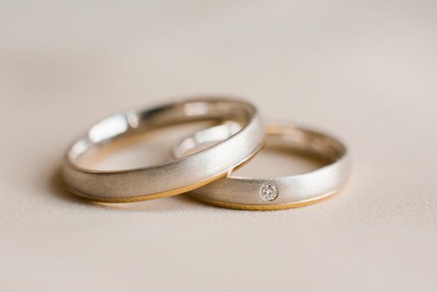 Wedding rings lie on beige Premium Photo