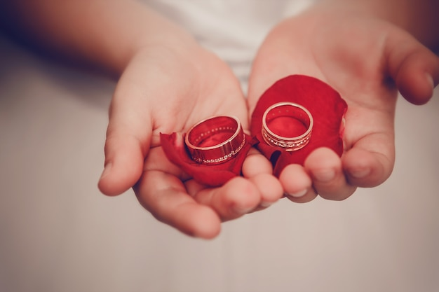 Wedding rings lie on children's palms with petals of roses Premium Photo