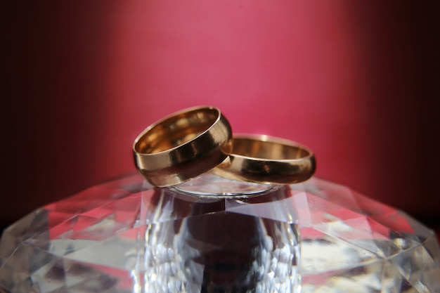 Wedding rings lie on a glass stand and on purple background Premium Photo
