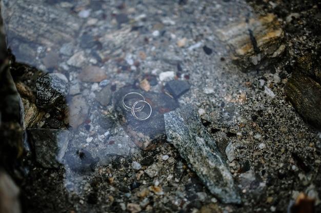 湖の底で水の下に横たわっている結婚指輪 Premium写真