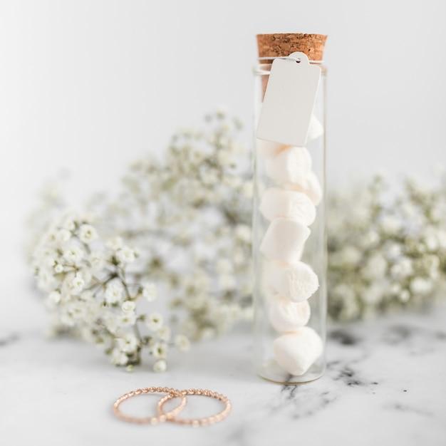 결혼 반지; 질감 된 배경에 태그와 아기의 숨 결 꽃 마쉬 멜 로우 테스트 튜브 무료 사진
