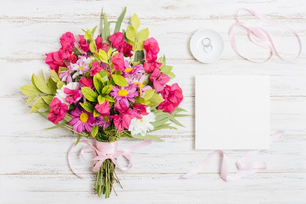 Wedding rings; ribbon and flower bouquet near white card on wooden desk Free Photo