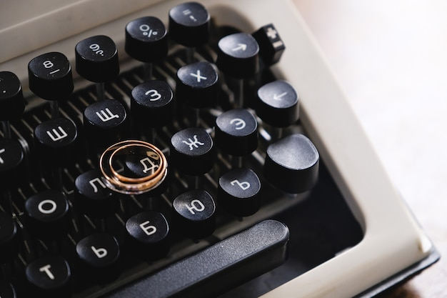 Wedding rings on the typewriter. wedding rings placed on an ancient typewriter letter buttons. Premium Photo