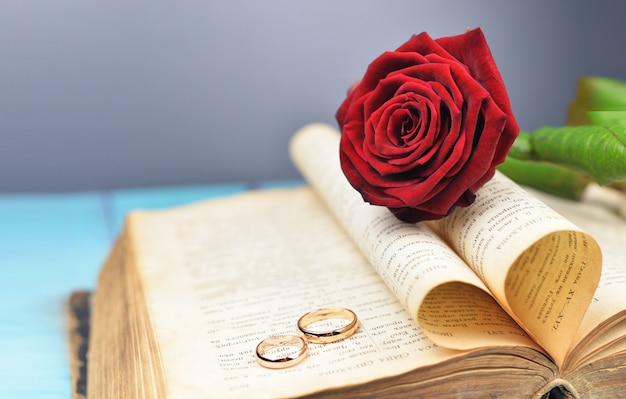 Wedding rings on a wedding with a red rose on an old book Premium Photo