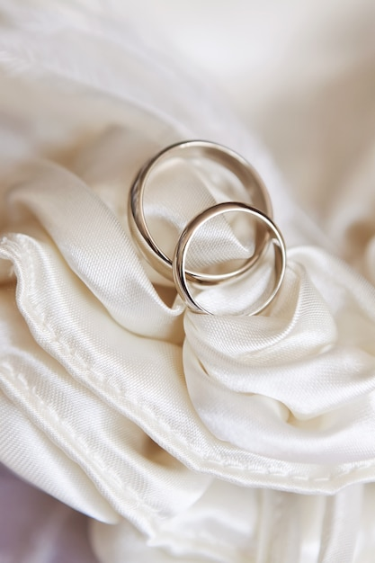 Wedding rings on white satin fabric Premium Photo