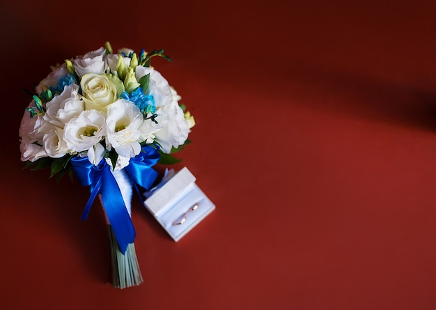 Wedding rings with a bridal bouquet of white roses Premium Photo