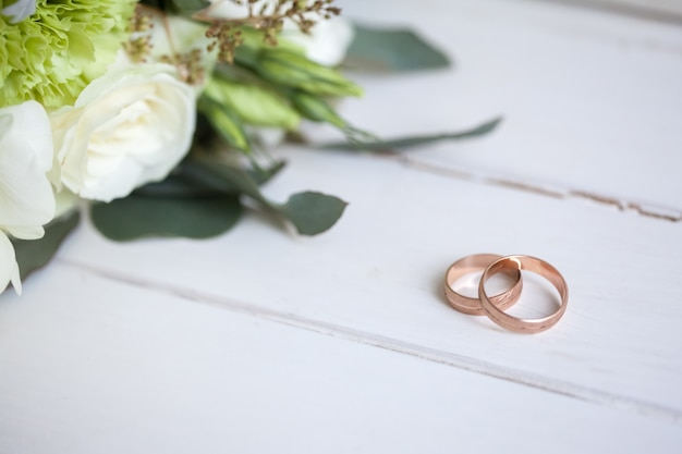 Wedding rings with white roses on wooden table Free Photo