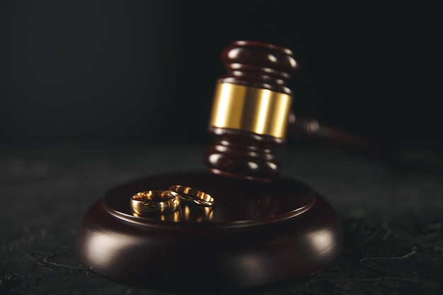 Wedding rings on wooden board and judge gavel Premium Photo