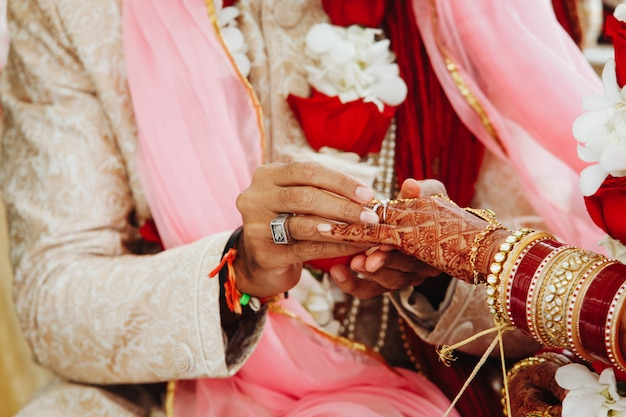 Wedding ritual of putting the ring on the finger in india Free Photo