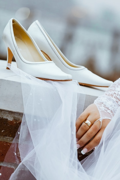 Wedding shoes with heels are hanging on a white fence before the bride puts them on for her wedding ceremony. Premium Photo