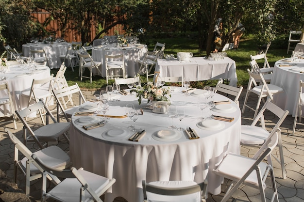 Wedding table setting. banquet table for guests outdoors with a view of green nature Premium Photo