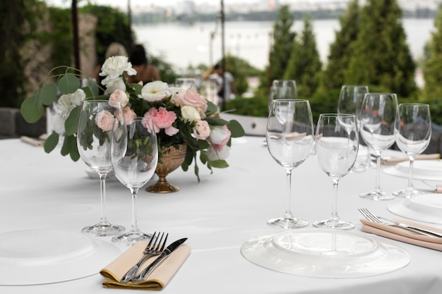 Wedding table setting decorated with fresh flowers in a brass vase Premium Photo