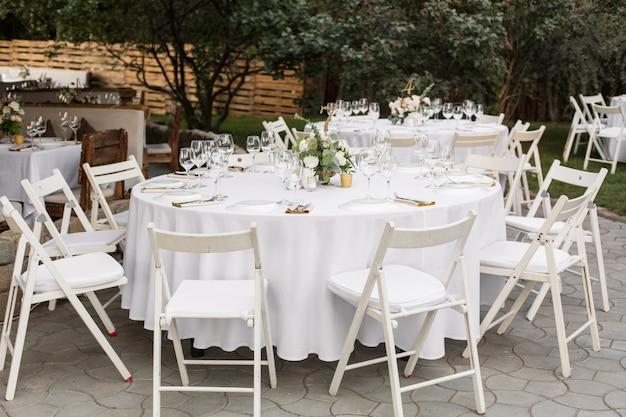Сервировка свадебного стола украшена живыми цветами в медной вазе Premium Фотографии