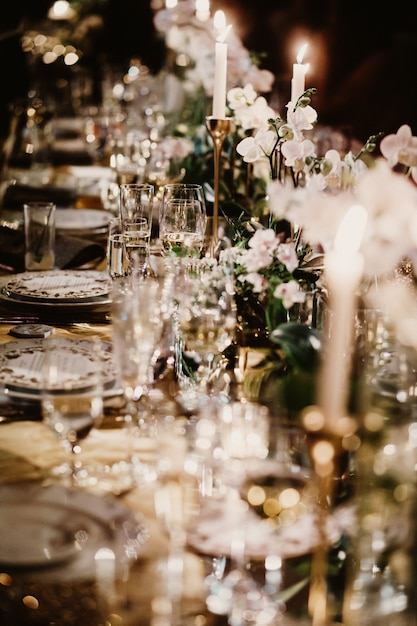 Wedding table with candles decorated with bouquets of flowers Free Photo
