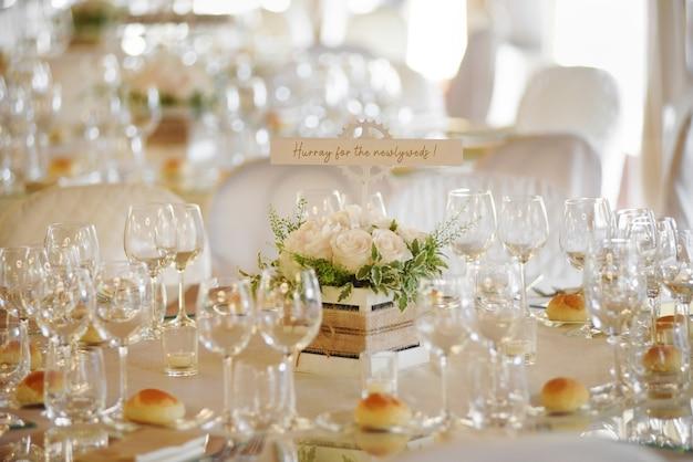 우아한 유리 제품과 작은 빵이 손으로 쓴 메시지와 함께 중앙을 감싸는 공식적인 테이블 세팅이있는 결혼식 장소 프리미엄 사진