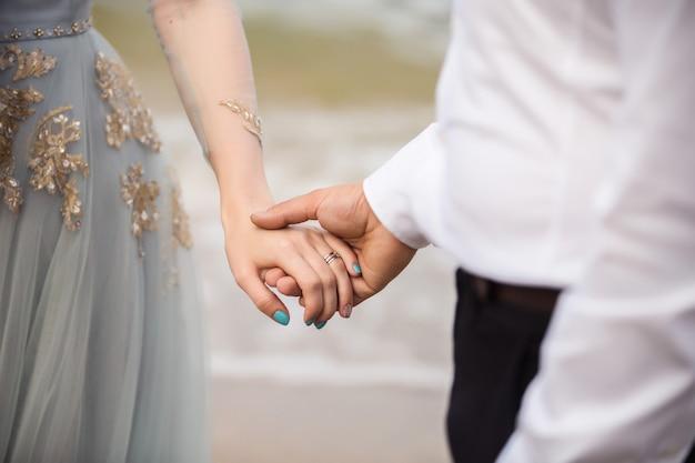 結婚式。海での結婚式。や海の背景にエレガントでスタイリッシュな青いウェディングドレスの花嫁の手を握って白いシャツの新郎。花嫁の結婚指輪の手に Premium写真