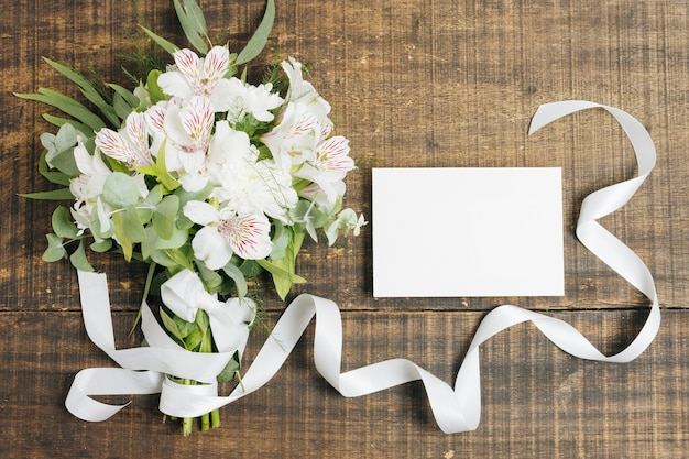 Wedding white card and peruvian lily flower bouquet tied with ribbon on wooden desk Free Photo