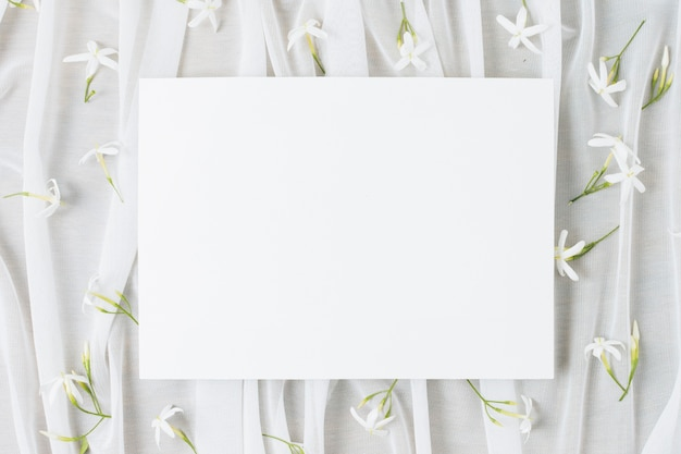 Wedding white placard surrounded with jasminum auriculatum flowers on scarf Free Photo
