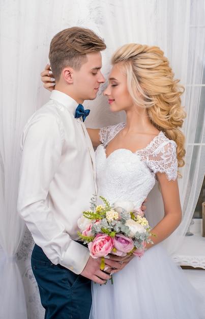 Свадьба с декором поцелуями, объятиями. счастливая пара. влюбленные невесты и жениха в роскошном декоре. жених и невеста вместе. пара обниматься. молодожены в день свадьбы Premium Фотографии
