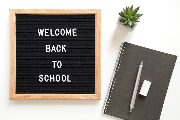 Welcome back to school text on slate near stationeries over white background Free Photo