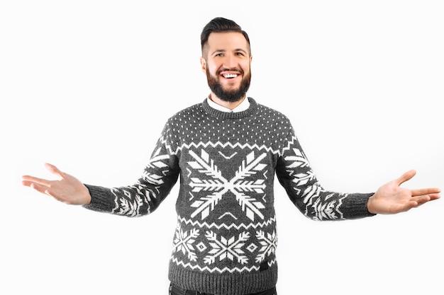 白い背景の上に立っているひげのジェスチャーと笑顔でハンサムな若い男を歓迎します Premium写真