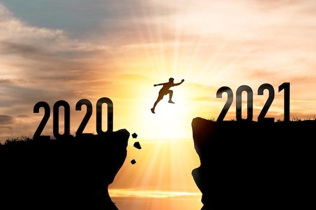 2021 년 메리 크리스마스와 새해 복 많이 받으세요, 2020 년 절벽에서 구름 하늘과 햇빛으로 2021 년 절벽으로 점프하는 실루엣 남자를 환영합니다. 프리미엄 사진