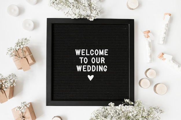 Welcome message on black frame surrounded with gift boxes; marshmallow test tubes; candles and flower on white backdrop Free Photo