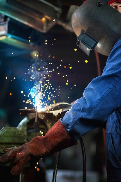 Сварщик сваривает в гараже, рабочий-рабочий на заводе сваривает стальную конструкцию Premium Фотографии