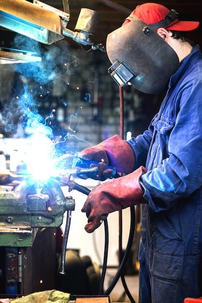 Сварщик сваривает металлическую часть в гараже. с защитной маской, сварщик промышленной стали Premium Фотографии