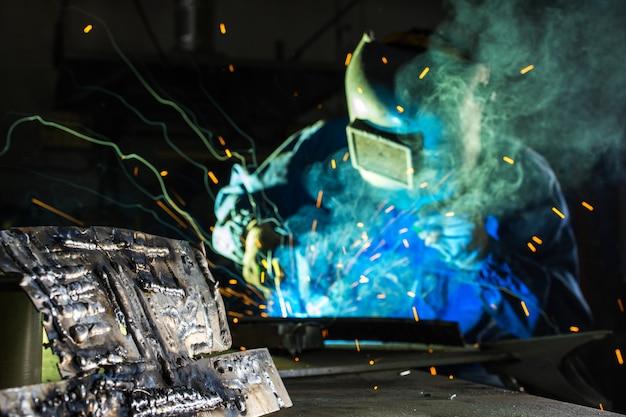 Сварка в производстве, электросварщик, работающий с аргоновой сваркой маски, работая над деталями Premium Фотографии