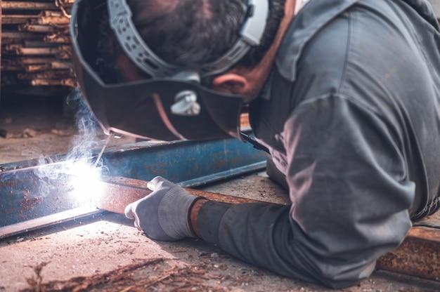 Сварочные работы, человек сварка в мастерской. металлоконструкции и искры.  строительство и промышленная концепция. | Премиум Фото