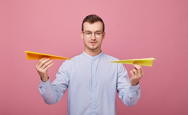 A well-bred young man in blue shirt and pc glasses stands with two paper airplanes in his hands Premium Photo