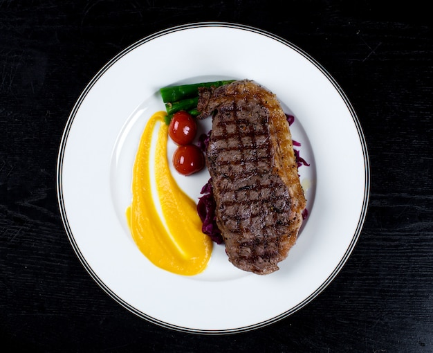 Well-done steak with cherry tomato and asparagus Free Photo